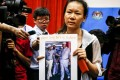 The wife of a missing Malaysia Airlines Flight MH370 passenger shows her husband's picture to reporters at a media conference room in Putrajaya, Malaysia. Photo: EPA