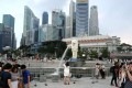 Tourists visit Singapore's Merlion Park as hotels struggle from a glut of rooms. Photo: Xinhua