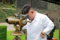 North Korean leader Kim Jong Un looking though binoculars at the site of a ballistic missile launching at an undisclosed location in North Korea. KCNA?via AP