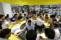 Employees serve customers at a service counter at a Reliance Digital store in New Delhi. Photo: Bloomberg