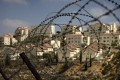 A Jewish settlement in the West Bank, seen through a barbed wire fence. Milton Viorst's book grapples with how Israel got itself into its current position. Photo: AP