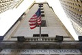 The American flag flies above the Wall Street entrance to the New York Stock Exchange. Photo: AP