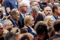 Democratic presidential candidate Hillary Clinton, centre, accompanied by Sen ator Chuck Schumer (left) and Representative Joseph Crowley (second from left) speaks with New York Mayor Bill de Blasio (centre right), during a ceremony at the September 11 memorial, in New York, on Sunday. Clinton left the event feeling ill. Photo: AP