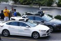 Uber employees stand by self-driving Ford Fusion hybrid cars while test driving the vehicles in Pittsburgh last month. Photo: AP