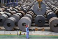 A roll of steel sheet is guided into position at a factory in Handan, Hebei province. Moody's notes that some provinces heavily exposed to excess-capacity industries such as coal, steel and basic manufacturing are lagging behind the national average. Photo: Reuters
