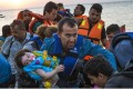 In this August 13, 2015 file photo, a man carries a girl in his arm as they arrive with other migrants and refugee just after dawn on a dinghy after crossing from Turkey to the island of Kos in southeastern Greece.Photo: AP