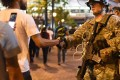 A protester shakes hands with a National Guard troop during a protest in Charlotte. Photo: EPA