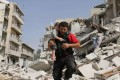 A Syrian man carries a toddler after rescuing him from the rubble of a destroyed building following a reported air strike in the Qatarji neighbourhood of Aleppo on Wednesday. Photo: AFP