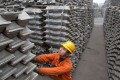 An worker checks aluminium ingots for export at the Qingdao Port, in Shandong province. Photo: Reuters