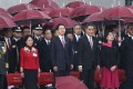 Hong Kong and Beijing officials attend a flag-raising ceremony on Saturday to celebrate National Day. From left: Major General Tan Benhong, head of the PLA's Hong Kong garrison; Tong Xiaoling, acting commissioner of the Ministry of Foreign Affairs in Hong Kong; Zhang Xiaoming, director of the central government's liaison office; Chief Executive Leung Chun-ying and his wife Regina Tong Ching-yi; and Chief Justice Geoffrey Ma Tao-li. Photo: Jonathan Wong