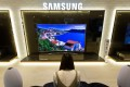 A visitor watches a Samsung Electronics Co. curved SUHD television at the company's D'light flagship store in Seoul, South Korea. Photo: Bloomberg