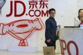 Visitors wait at the entrance to JD.com head office in Beijing. JD.com has grown into Chinas biggest Internet-based direct retailer. Photo: AP