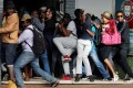 Students demanding free education react as they are fired at by riot police during a protest outside the University of the Witwatersrand in Johannesburg, South Africa on Monday. Photo: Reuters
