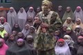 An alleged Boko Haram soldier standing in front of a group of girls alleged to be some of the 276 abducted Chibok schoolgirls held since April 2014, in an unknown location. Photo: AP