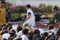 A mourner is attended to after passing out while waiting for the motorcade carrying the body of King Bhumibol Adulyadej. Photo: Reuters