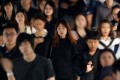 Commuters dressed in black and white or dark coloured clothes, to mourn the passing of Thailand's King Bhumibol Adulyadej, head to work during morning rush hour in Bangkok Monday. Photo: Reuters