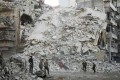 Members of the Syrian Civil Defence, known as the White Helmets, search for victims amid the rubble of a destroyed building following air strikes in the rebel-held Qatarji neighbourhood of Aleppo on Monday, ahead of a ceasefire announced by Russia. Photo: AFP