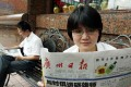 A file picture of a woman reading the Guangzhou Daily on the street. Photo: SCMP Pictures