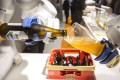 A Kuka industrial robotic arm pours a glass of beer during a trade fair in Munich, Germany, in June. Photo: Bloomberg