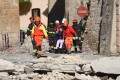 Italian fire fighters help a resident in the town of Norcia after Sunday's strong earthquake in central Italy. Photo: EPA