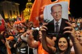 Lebanese celebrate the election as president of Michel Aoun (pictured in portrait), a former general backed by the powerful Hezbollah movement, in downtown Beirut on Monday. Photo: AFP