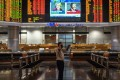 A trader in Kuala Lumpur in front of an electronic board showing stock movements during the US presidential vote. Photo: AFP