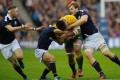 Australia's Lopeti Timani is tackled against Scotland at Murrayfield. Photo: AFP