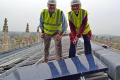 Canon Celia Thomson bolts in the first solar panel on top of Gloucester Cathedral, in south west England. Photo: Mypower