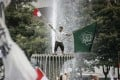 An Indonesian protester waves flags as he stands on a fountain during a protest against allegedly blasphemous remark made by Jakarta's Governor Basuki Tjahaja Purnama. Photo: EPA