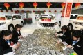 Staff counting the cash at the car dealership. Photo: Sina.cn