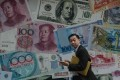 A man walks past a display showing bank notes of different currencies in Hong Kong. Photo: AFP