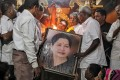 Well wishers of Tamil Nadu Chief Minister Jayalalithaa Jayaraman hold her portrait as they pray at a temple in Mumbai, India. Photo: Reuters
