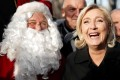 Far-right leader and candidate for next spring presidential elections Marine le Pen poses with Santa Claus during a visit to Champs Elysees Christmas market in Paris on Thursday, December 8, 2016. Photo: Reuters
