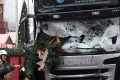 Firefighters stand next to a damaged truck that ran into a crowded Christmas market the evening before and killed several people. Photo: AP