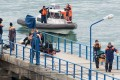 Russian rescuers carrying the belongings of passengers aboard the Russian military plane that crashed in the Black Sea, on a pier outside Sochi. Photo: AFP