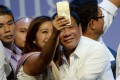 Philippines President Rodrigo Duterte poses for a selfie during a meeting with the Filipino community in Singapore during a two-day state visit. Photo: AFP