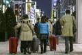 Chinese tourists carry suitcases packed with purchases after bulk buying, or 'Bakugai' in central Tokyo. Chinese tourists' shopping makes a large contribution to the Japanese economy. Photo: EPA