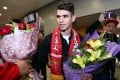 Brazilian football player Oscar receives flowers as he arrives at Shanghai airport on January 2. Photo: AFP