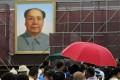 Mao Zedong's portrait hangs above tourists visiting Tiananmen in Beijing. Photo: Xinhua