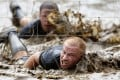 Competitors swim through mud underneath electrified wires during a Tough Mudder. Photo: Reuters
