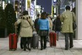 Chinese tourists carry suitcases packed with purchases during bulk buying, known as Bakugai, in central Tokyoin 2015. Photo: EPA