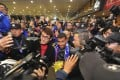 Carlos Tevez is mobbed at Shanghai's Pudong airport as he arrives to start collecting a weekly wage reported to be US$800,000. Photo: AP