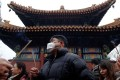 Grey skies hang over Lunar New Year revellers at the Yonghegong Lama Temple in Beijing on Saturday. Photo: Reuters