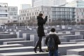 Visitors take photos while standing on the blocks of the Memorial to the Murdered Jews of Europe in Berlin last Thursday. Photo: EPA