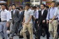 Japanese businessmen walk to their offices in Tokyo. Photo: AFP