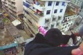The husband holds on to his wife's hair as a police officer tries to grab her. Part of her body weight was also supported by a pipe at the edge of the building. Photo: Sohu.com