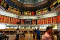 Investors monitor share prices from electronic display boards of the Kuala Lumpur Stock Exchange at the RHB trading floor in Kuala Lumpur. Photo: Jimin LAI/AF