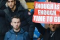 An Arsenal fan holds up a banner calling on manager Arsene Wenger to quit. Photo: AFP