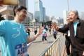 John Tsang greets runners of the Hong Kong marathon on Sunday. Photo: Felix Wong
