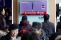 Passengers watch a TV screen broadcasting a news report on North Korea firing a ballistic missile into the sea off its east coast, at a railway station in Seoul, South Korea, on February 12. Photo: Reuters